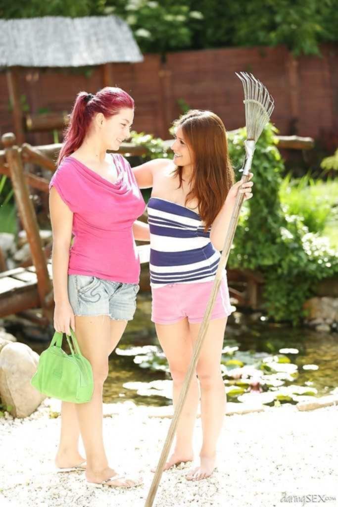 Две красотки ласкают друг друга на зеленой травке во дворе